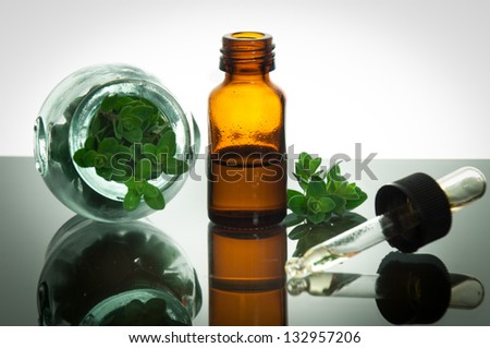 Essential oil with oregano leaves - stock photo