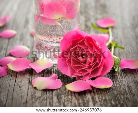 Essential oil with rose petals on wooden background - stock photo