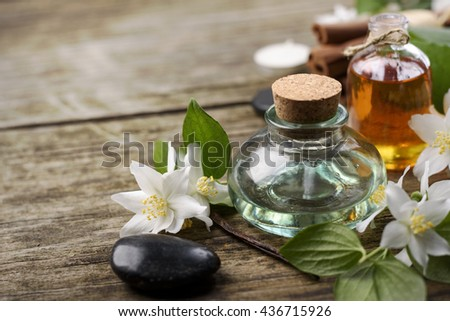 Essential oils with jasmine, cinnamon and vanilla on rustic wooden table, - stock photo
