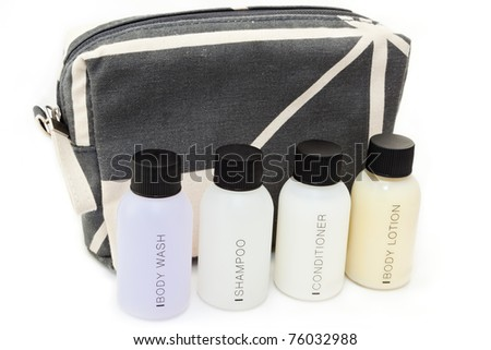Essential travel toiletries in front of a grey, patterned bag. - stock photo