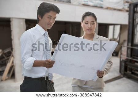 Estate agent buyer looking blueprint against stock photo 388547842 estate agent and buyer looking at blueprint against workshop malvernweather Images