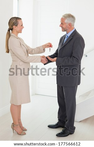 Estate agent giving house key to happy customer in empty house