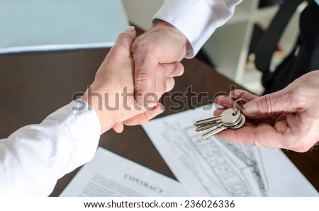 Estate agent giving house keys to customer after contract signature - stock photo
