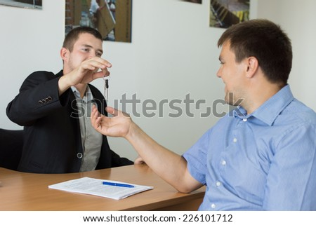 Estate agent or car salesman completing a deal and handing over the keys to the new purchaser in his office - stock photo