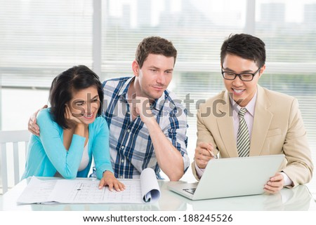 Estate agent presenting a house to the young couple by using a laptop - stock photo