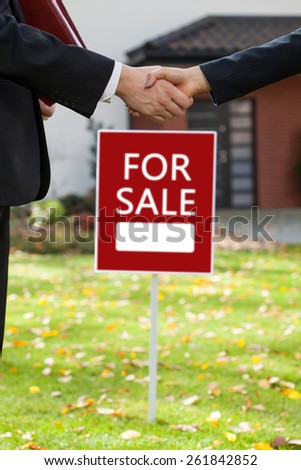 Estate agent sells the house and shaking hand of client - stock photo