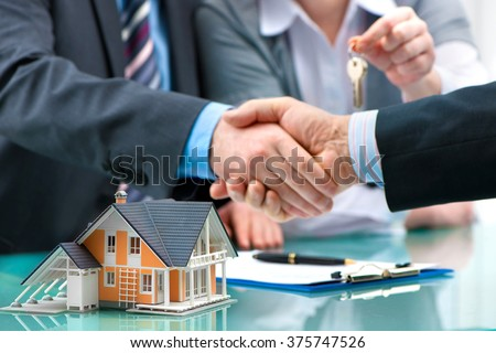 Estate agent shaking hands with customer after contract signature - stock photo