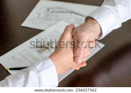 Estate agent shaking hands with his customer after contract signature - stock photo