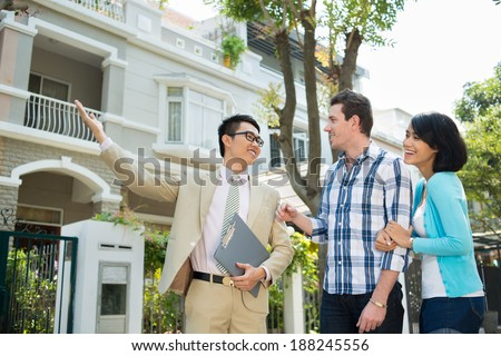 Estate agent showing a house to the young family - stock photo
