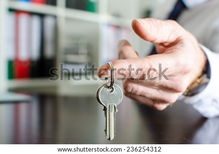 Estate agent showing house keys on a wooden table - stock photo