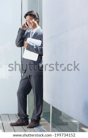 Estate agent talking on phone outside a house