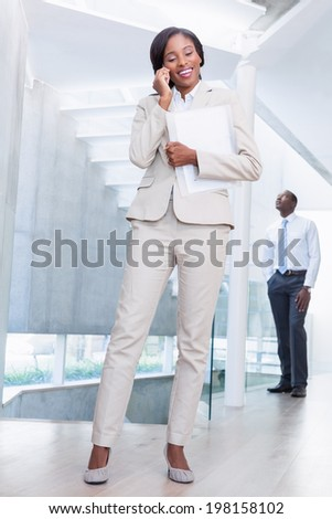 Estate agent talking on phone with buyer in background in a new house - stock photo