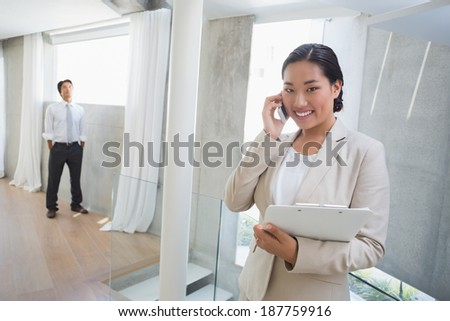 Estate agent talking on phone with buyer in background in the hallway - stock photo