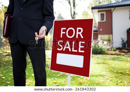 Estate agent with keys and sign outside the house