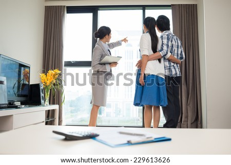 Estate broker showing married couple the view from the apartment window - stock photo