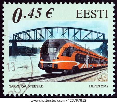 ESTONIA - CIRCA 2012: A stamp printed in Estonia shows Railway Bridge of Narva, Estonia and Stadler FLIRT type passenger train, circa 2012. - stock photo