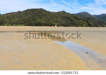 Estuary beach and wooded hills of Abel Tasman National Park, New Zealand - stock photo