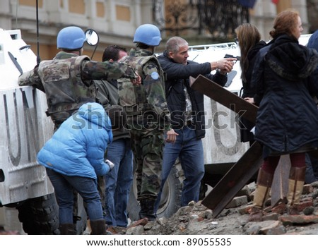 ESZTERGOM, HUNGARY - NOV 10: While Angelina Jolie looks on, her bodyguard instructs actors how to use a pistol on the set of  In The Land Of Blood And Honey Esztergom, Hungary, on Wednesday, November 10, 2010.