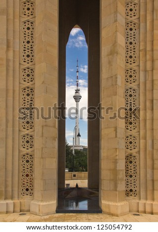 Eternal flame memorial, Baku, Azerbaijan.  Chalk-stone memorial is 21 metres high and capped by a glass cupola. Telecoms tower in the distance. - stock photo