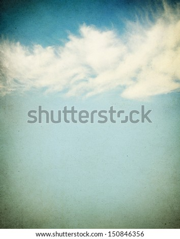 Ethereal and puffy clouds on a grunge paper background.  Image has a distinct paper grain and texture. - stock photo