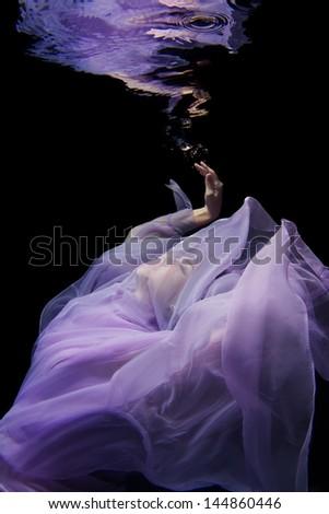 Etherial Portrait of an Underwater Model in a Purple Dress - stock photo