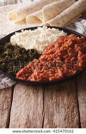 Ethiopian cuisine: kitfo with herbs and cheese on a plate and injera. Vertical
