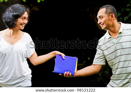 ethnic asian students hand over stack of books - stock photo