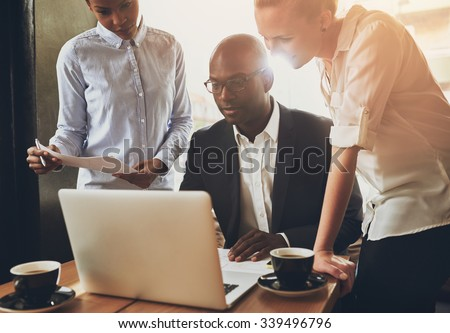 Ethnic business people, entrepreneurs working together using a laptop - stock photo