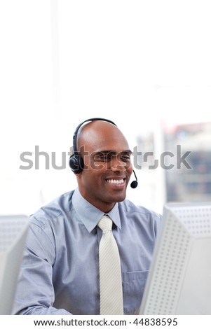 Ethnic businessman with headset on working at a computer - stock photo