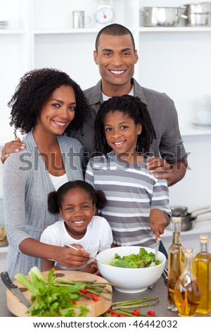 Ethnic family preparing salad together in the kitchen - stock photo