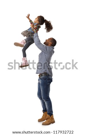 Ethnic father throwing little daughter in the air, having fun, laughing. - stock photo