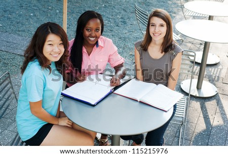 Ethnic group of girls outside studying and smiling - stock photo