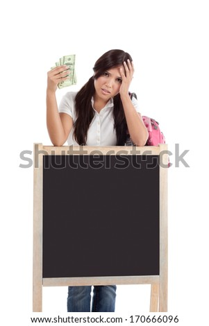 Ethnic Hispanic college student with notebook and backpack holds pile 100 (one hundred) dollar bills money frustrated by exuberant raising tuition cost and unaffordable education forcing into debt - stock photo