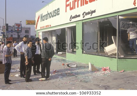 Ethnic men observing furniture store looted during 1992 riots, South Central Los Angeles, California - stock photo