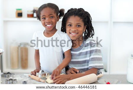 Ethnic siblings making biscuits in the kitchen - stock photo