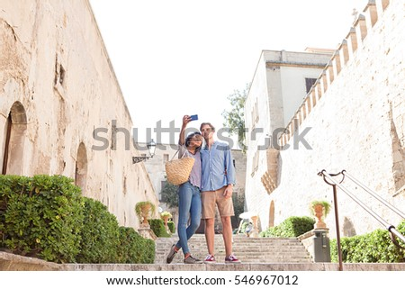 Ethnically diverse beautiful tourist couple visiting a destination city on holiday, using smart phone taking selfies pictures on a sunny day, together outdoors. Travel technology lifestyle, exterior.