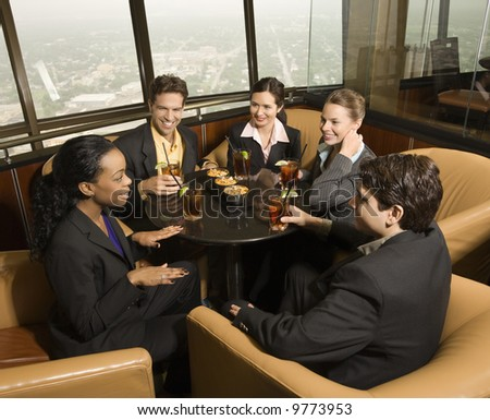 Ethnically diverse businesspeople sitting at table in restaurant talking. - stock photo