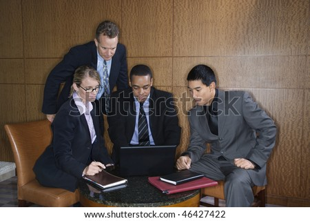 Ethnically diverse group of businessmen and a businesswoman look at a laptop computer screen. Horizontal shot. - stock photo