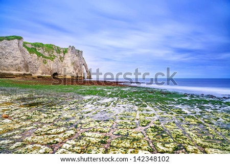 Etretat Aval cliff landmark and its beach in low tide under a cloudy sky. Normandy, France, Europe. Long exposure. - stock photo