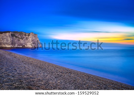 Etretat Aval cliff landmark and its beach Twilight  photography. Normandy, France, Europe. Long exposure. - stock photo