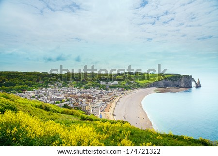 Etretat village, beach and Aval cliff landmark on ocean. Aerial view. Normandy, France, Europe. - stock photo
