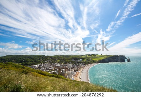 Etretat village, its bay beach and Aval cliff landmark. Aerial view. Normandy, France - stock photo
