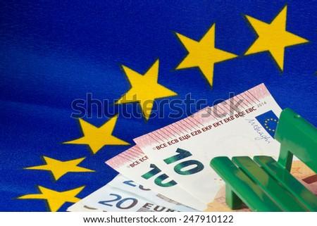 EU flag, Euro notes and bench - stock photo