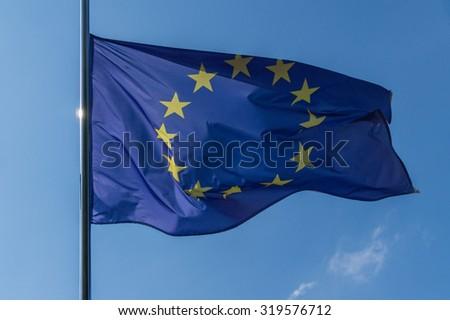 EU flag on a flagpole on a sky background - stock photo