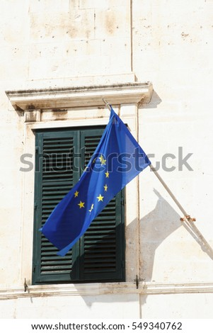 EU flag on the background of windows with shutters close-up. vertical