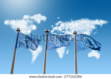 EU flags against world map made of white puffy clouds on blue sky - stock photo