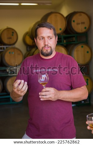 EUGENE, OR - JULY 17, 2014: Master brewer at Oakshire Brewing sampling and tasting bourbon barrel aged beers at the brewery. - stock photo