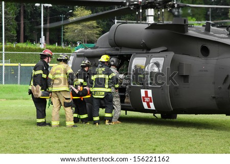 Eugene, Oregon, USA Â?Â? May 2, 2012: In Eugene, OR local Emergency Services and National Guard work together in a disaster response drill. Unidentified firemen carry an injured person to the helicopter. - stock photo