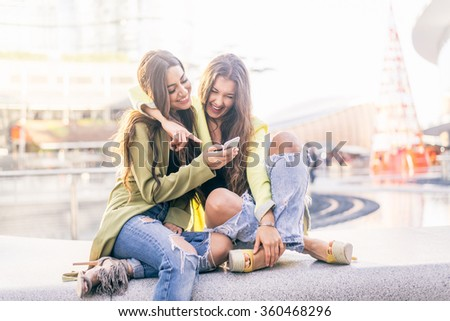 Euphoric friends watching videos on a smartphone and pointing at screen surprised - Girlfriends laughing and having fun outdoors - stock photo