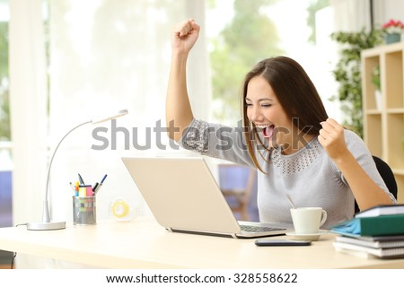 Euphoric winner watching a laptop on a desk winning at home - stock photo